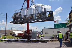 A crane lifts the carbon treatment system into place. This technology treats vapor pumped to the surface by the belowground heating system.