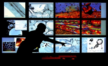 NREL Scientist Bryon Donohoe looks at different views of ultra structures of pre-treated biomass materials in the Cellular Visualization room of the Biomass Surface Characterization Lab. | Photo by Dennis Schroeder, NREL.