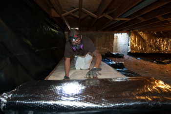 David Poindexter installs moisture barrier and insulation into the crawl space of a Lakewood, Colorado home. | Photo by Dennis Schroeder, National Renewable Energy Laboratory