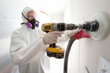 A weatherization worker drills holes to blow cellulose insulation in the interior walls of this home.   Photo courtesy of Dennis Schroeder, NREL