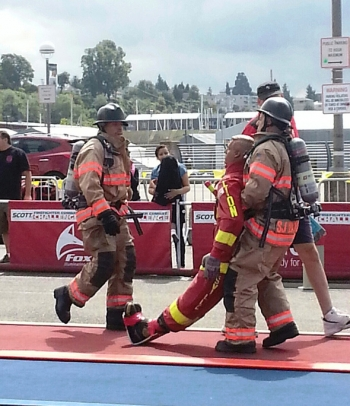 Hanford Fire Department Lt. Anthony Lovato, Jr. (left) urges his teammate, Capt. Sean Barajas, to carry the 175-pound life-sized dummy across the finish line at the Scott Firefighter Combat Challenge in Everett, Wash.