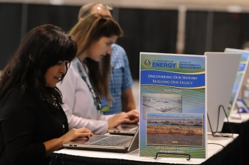 Visitors to EM's booth at the annual Waste Management Symposia international conference participate in demonstrations of the new timeline.