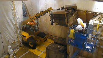 The box retrieval forklift carriage is used to lift a degraded box as retrieval personnel monitor progress.
