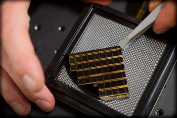 At NREL's High-Intensity Pulse Solar Simulator, NREL's Keith Emery removes an array of multijunction solar cells produced by PV Incubator partner Solar Junction. The NREL instrument can produce the intensity of up to 90 suns. | Photo credit: Dennis Schroeder