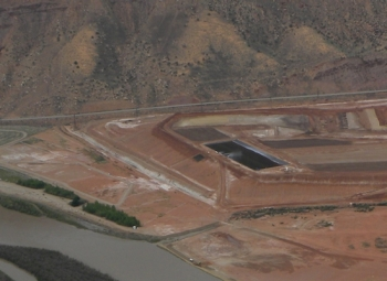 View of the evaporation pond (right center) on the tailings pile with the forced-air evaporators running. The extraction wells are between the pile and the Colorado River, which can be seen in the lower left.