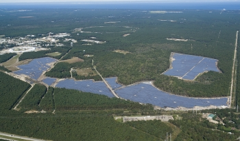 An aerial view of the 32-megawatt photovoltaic array of the Long Island Solar Farm, which will produce enough energy to power up to 4,500 local homes. The central Brookhaven National Laboratory campus is seen at left.