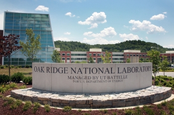 Oak Ridge National Laboratory's main entrance is marked by a limestone sign. Several new buildings visible in the background house more than 1,000 of the lab's 4,300 employees. | Photo courtesy of Oak Ridge National Laboratory