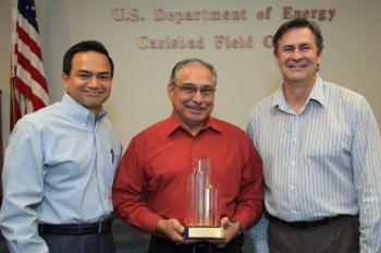 Department of Energy Carlsbad Field Site Operations Director Casey  Gadbury (right) and Farok Sharif, President and Project Manager for Nuclear Waste Partnership  LLC, the management and operating contractor at the Waste Isolation Pilot Plant, present the  DOE's Voluntary Protection Program Legacy Star Award to Richard De Los Santos, protective force manager for Security Walls, the security contractor at the Waste Isolation Pilot Plant. The DOE-VPP legacy star award is the highest level of recognition possible in the VPP.