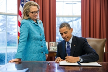 "Secretary of State Hillary Rodham Clinton watches as President Barack Obama signs a Presidential memorandum, ""Coordination of Policies and Programs to Promote Gender Equality and Empower Women and Girls Globally,"" in the Oval Office, Jan. 20, 2013. (Official White House Photo by Pete Souza)"