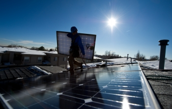 Workers install a solar energy system on the rooftop of a home in Golden, Colorado. More than 4,751 megawatts of solar power was installed in the United States last year, an increase of 41%.   Photo by Dennis Schroeder, National Renewable Energy Laboratory