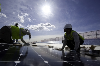 Workers install photovoltaic modules on top of a parking structure at National Renewable Energy Laboratory in Golden, Colorado. The Energy Department has several training resources for energy and manufacturing workers.   Photo by Dennis Schroeder, National Renewable Energy Laboratory