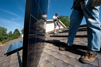 Brian Webster (left) and Mario Richard install photovoltaic modules on an Englewood, Colorado, home.   Photo by Dennis Schroeder, NREL.