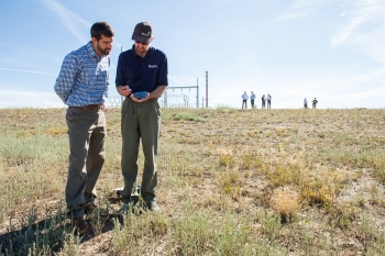 NREL's Otto VanGeet (right) shows James Jensen of Southern Ute Alternative Energy how to use a SunEye tool to check solar availability of the site. Photo by Dennis Schroeder, NREL
