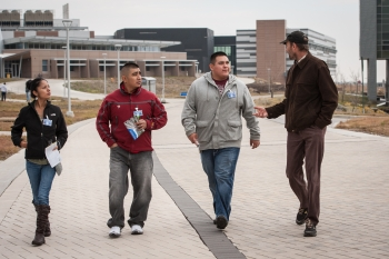 From left to right, Reyna Banteah, Shaun Tsabetsaye, and Jeremy Laselute of Zuni Pueblo, with NREL's Otto VanGeet. Photo by Dennis Schroeder, NREL
