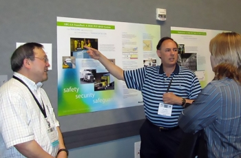 James Shuler, manager of DOE's Packaging Certification Program, within EM's Office of Packaging and Transportation, discusses the radiofrequency identification technology he developed. At left is RFID Team Leader Yung Liu, with Argonne National Laboratory.