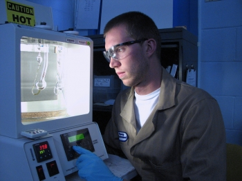 Intern Aleksander Navratil, Carroll College, is setting up to perform viscosity measurements of engine oil formulations for an Argonne National Laboratory program researching oils and additives to improve engine efficiency and reduce emissions. | Photo courtesy of Argonne National Laboratory.