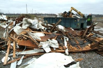 Workers cut up old trailers and placed them in containers so that the debris could be placed in the site's industrial landfill.