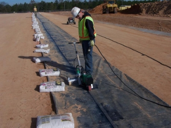 The liner installer heat-welds a sand anchor closed. The sand anchors are installed under the liner and across the length of the slit trench to keep the liner in place and minimize the effects of wind lift.