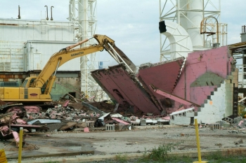 Heavy equipment demolishes the last part of the eastern third of the Feed Plant at the Paducah Site. Cleanup continues to prepare the remaining part of the complex, background for demolition later.