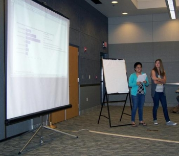 NSSAB student liaisons Gumabon, left, and Leavitt discuss their project involving a student survey and educational tool to members of the NSSAB.