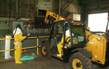 Forklift operatorA spotter, left, helps a forklift driver safely drop debris into a roll-off bin in the Feed Plant.