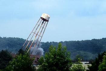 Oak Ridge's K-1206 F Fire Water Tower falls into an empty field during a recent demolition project.