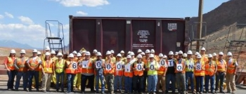Moab site workers stand in front of the container holding the 6 millionth ton.