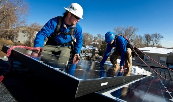 Kyle Travis, left and Jon Jackson, with Lighthouse Solar, install microcrystalline PV modules on top of Kevin Donovan's town home. | Credit: Dennis Schroeder.