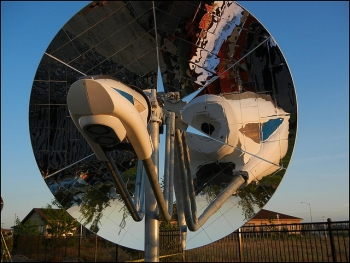 In the photo above, a mirrored parabolic dish directs sunbeams to a central point, where a device absorbs the solar heat to make syngas, solar-boosted natural gas. This new system was recognized with a 2014 R&D 100 Award. | Photo courtesy of Pacific Northwest National Lab.