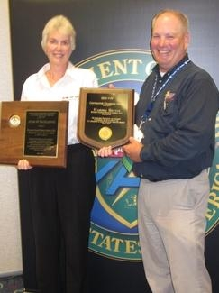 Wastren-EnergX Mission Support (WEMS) Senior Safety Engineer Marsha Bevins, left, stands with DOE Director of Worker Safety and Health Brad Davy while holding her Voluntary Protection Program Contractor Champion of the Year award and the 2012 Star of Excellence award WEMS received.
