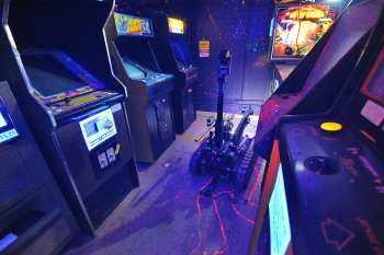 In the photo above, a robot investigates a bomb threat at an arcade during the 2013 Robot Rodeo at Sandia Labs. The operators are not allowed to turn on the lights or turn off the machines, complicating the operation. | Photo by Randy Montoya, Sandia National Laboratories.