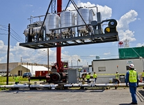 Employees lower a carbon treatment system into place to remove groundwater contamination from near an equipment cleaning building in the middle of the Paducah site.