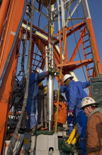 Schlumberger technicians and rig crew lowering monitoring instrumentation into a well. | Photo credit to the Illinois State Geological Survey.