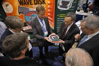 Steven Chu, Secretary of the United States Department of Energy, holds a model of the wave disk engine at the 2011 ARPA-E Summit's Technology Showcase. | Photo by Ken Shipp.