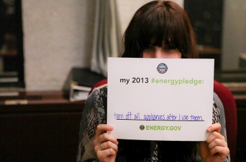 Download your own pledge card and submit a photo -- you might see yourself on energy.gov/pledge! Here, Amanda pledges to turn off all appliances when she's not using them to save energy. | Energy Department photo.