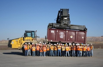 The day crew at the Crescent Junction Disposal site stands in front of the container carrying the 4 millionth ton of mill tailings from the Moab site.