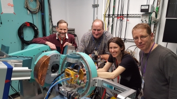 The SLAC/NREL research team poses with the rapid thermal processing instrument at SLAC, which allowed them to uncover how contact paste performs in solar modules.
