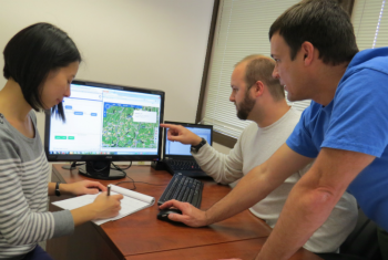 Workers from Clean Power Research review a software platform that aims to lower the costs associated with connecting distributed solar electricity generation to the grid. The platform is one of several projects funded through the Energy Department's SunShot Incubator Program, which provides early-stage assistance to help small businesses cross technological barriers to commercialization.  | Photo courtesy of Clean Power Research