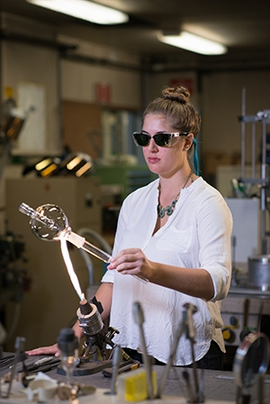 Babbitt demonstrates her scientific glass technology skills.
