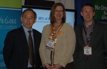 Secretary Steven Chu with Kellie Walsh and Cris Dorman of Greater Indiana Clean Cities at the Green Truck Summit in Indianapolis, IN, in front of a display describing the coalition's Recovery Act-supported project.   Photo by Trish Cozart, NREL.