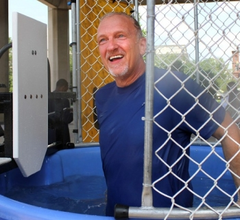 Senior Advisor for Environmental Management David Huizenga stands after falling into a dunk tank during an event to collect nonperishable food items for the DOE Feeds Families campaign.