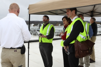 On the roof of the Cummins plant, tour participants take a peek at a new 2 MW solar panel installation. From left to right: Dennis Phillips, the Jamestown Post Journal, Maria Vargas, DOE, Andre de Fontaine, DOE, Mike Abbate, Cummins.  Photo courtesy of Cummins Inc.