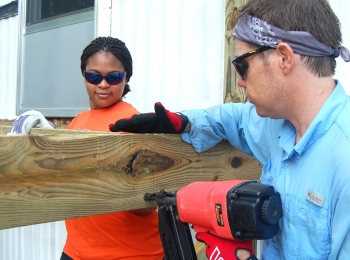 James Cunningham, right, nails a board to the framework for a deck project in Jackson. Ashley Flowers, Savannah River Remediation project controls intern, assists by holding the board in place.