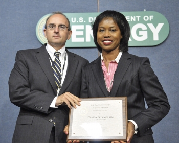 Shelton Clark, President of Eberline Services, receives the Small Business of the Year award from Dot Harris, Director of the Office of Economic Impact and Diversity. Eberline Services, a New Mexico-based small business, gets 90% of their business from the Energy Department. They specialize in radiological protection and environmental services. | Photo by Charles Watkins, DOE Photographer.