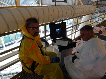 Frank Carney from Manta Robotics (left) and Kirk Barlow, BWCS systems engineering manager, use a monitor to see inside the tank.