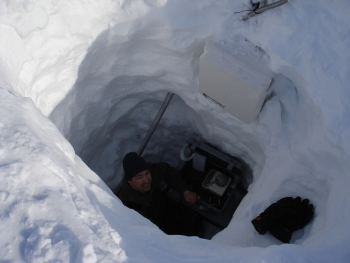 Researcher Joel Bailey measures the density of the snow in this snow pit to determine the amount of snow in the drift and the water equivalent of the snow drift.