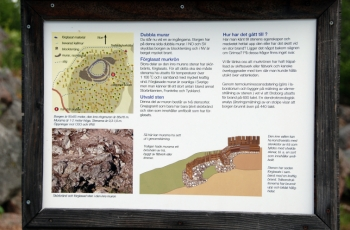 A sign at a hillfort site explains, in the Swedish language, how the hillfort was constructed and how glass material was made at the site.