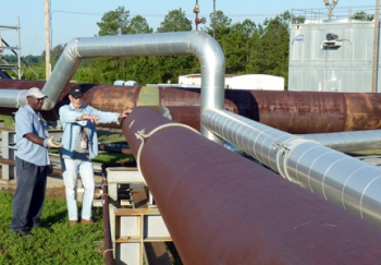 Harrel McCray, left, and Joey Clark, employees with SRS management and operationscontractor, Savannah River Nuclear Solutions, stand by an extensive SRS cleanup system thatsafely and successfully rid the site of more than 33,000 gallons of non-radioactive chemicalsolvents from 10 million cubic feet of soil through the injection of millions of pounds of steam.