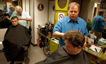 Ron Wilson, left, cuts Joe Conklin's hair while David Besenyei prepares to trim the hair of another customer.   Energy Department Image   Photo by Hantz Leger, Contractor