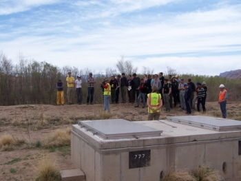 As Durham University students stand on the bank of the Colorado River, Moab Groundwater Manager Ken Pill (in yellow vest at left) explains how the groundwater interim action system operates. A well vault is in the foreground.